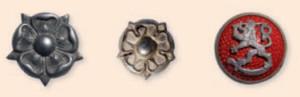 """Reserviupseerin hopean väriset arvomerkit eli """"tinanapit"""" ja reserviupseerin hopealeijonainen päähinekokardi """"mansikka"""". Nämä merkit olivat reserviupseerin tunnuksina vuoteen 1941 asti."""