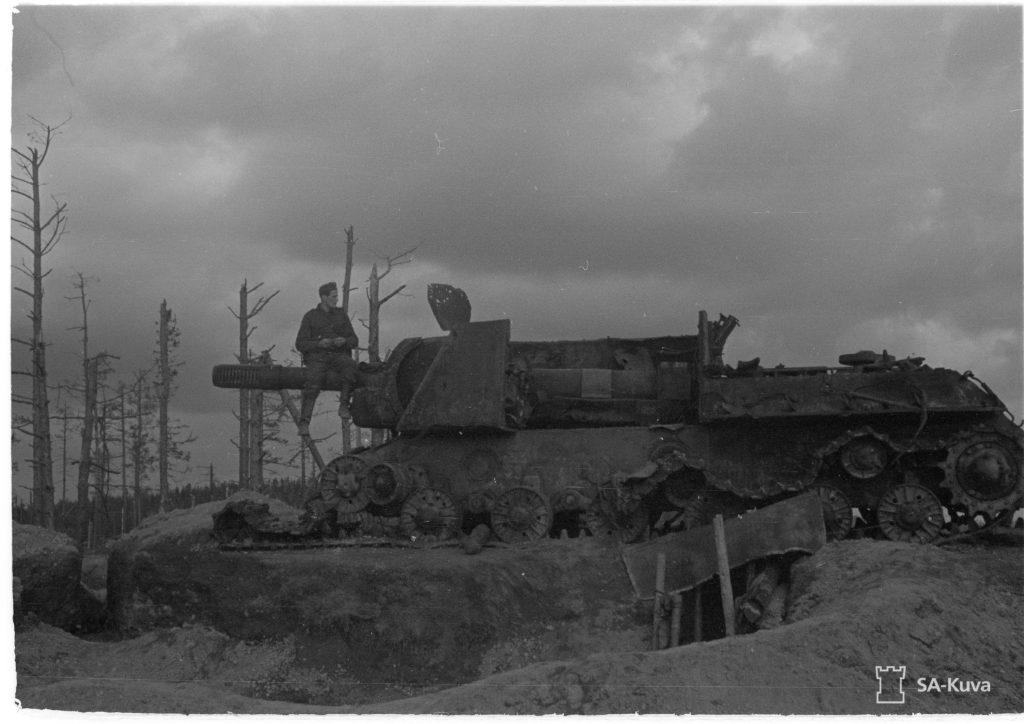 """Panssari on torjuttu! """"Kuuden tuuman (152 mm) rynnäkkötykki on kohdannut matkansa pään """"""""panssarinyrkin"""""""" iskusta. Pystyssä olevan kansiluukun alapuolella olevassa sivupanssarissa näkyy """"""""nyrkin"""""""" sisäänmenoreikä,"""" kertoo alkuperäinen kuvateksti Sa-kuvassa. Lähde mukaan matkaamme katsomaan miten punapanssarit pysäytettiin!"""